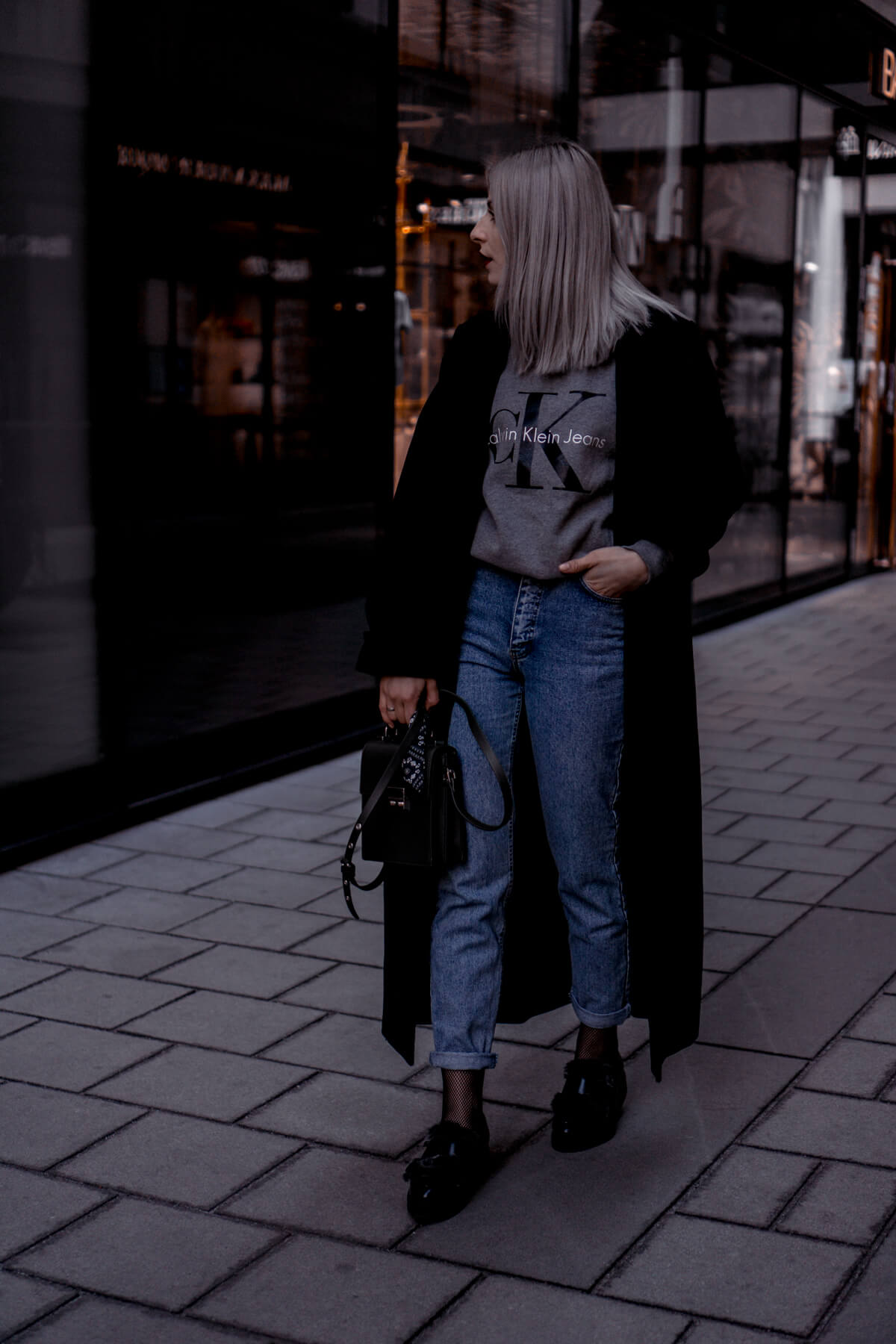 Fashion Blogger wearing fishnet tights, mom jeans, logo sweater and mom jeans
